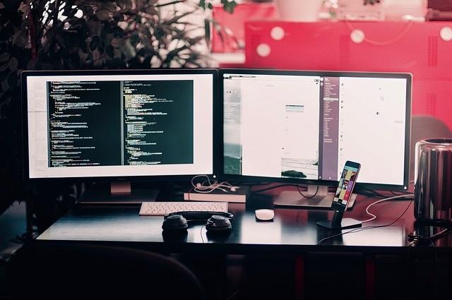 Computer-Monitore auf einem schwarzen Schreibtisch